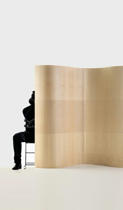 man sitting on chair behind flexible wall